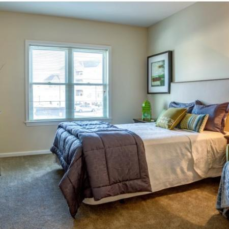 Large furnished bedroom with wall-to-wall carpeting and large window with mini-blinds. Room contains bed, dresser, two nightstands and chair.