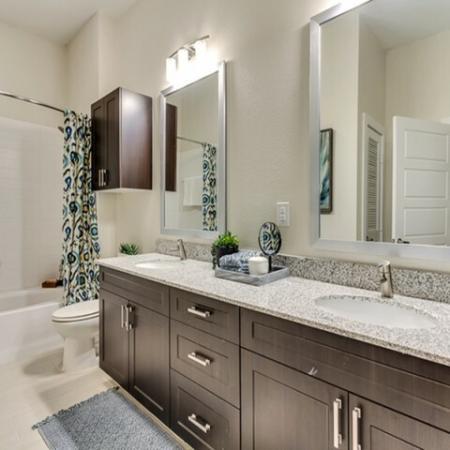 Bathroom with Double Vanities, Granite Countertops, and Garden Soaking Tub