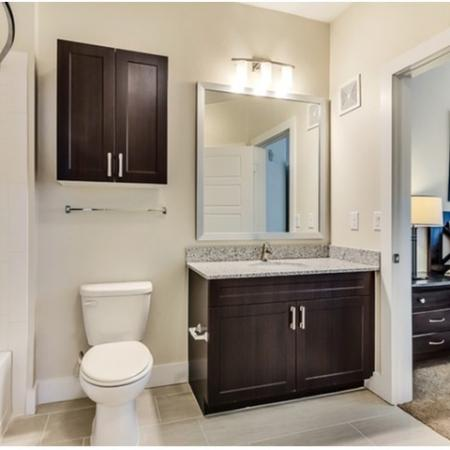 Bathroom with Single Vanity with Granite Countertops and Oversized Bathroom Mirror