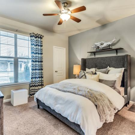 Large bedroom with carpet and ceiling fan