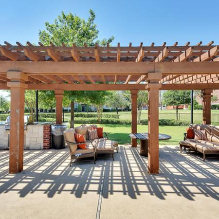 BBQ grills located right next to a beautiful outdoor lounge covered by a cabana