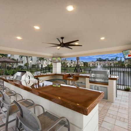 Covered open air outdoor grilling area with 2 stainless steel grills, ceiling fans, ample bar seating and fountain view