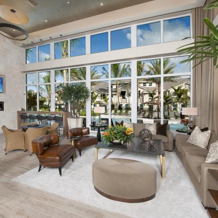 Indoor lounge seating with couches, chairs and TV. View of pool area with large open windows
