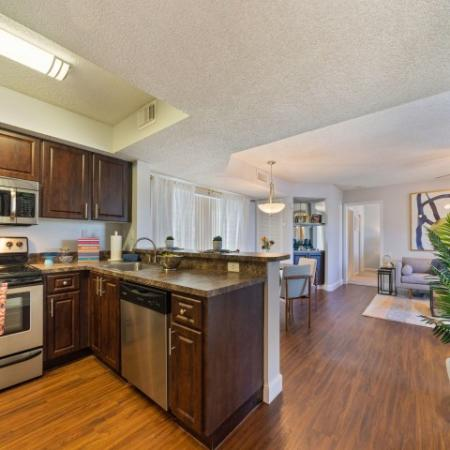 Kitchen with cabinets, sink, stainless steel microwave, oven, and dishwasher looking into dining and living room