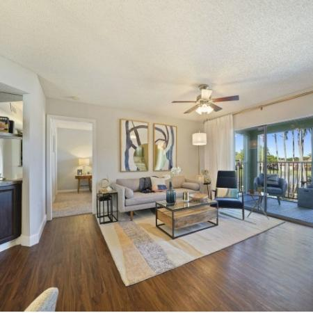 Furnished living room with couch, chair, end table, coffee table, ceiling fan, and balcony door