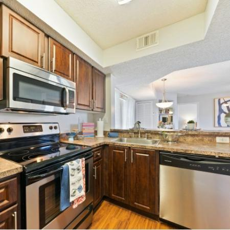 Kitchen with cabinets, sink, stainless steel oven, microwave, and dishwasher overlooking living room