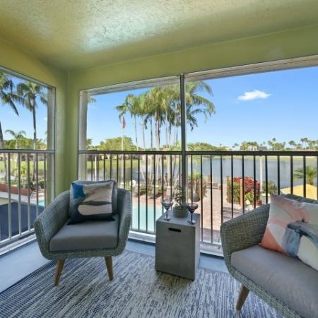 Large, screened patio with two chairs and small table overlooking lake