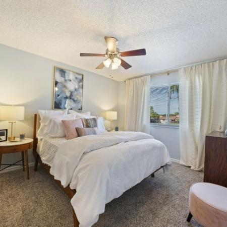 Furnished bedroom with bed, two nightstands, stool, dresser, ceiling fan, and window