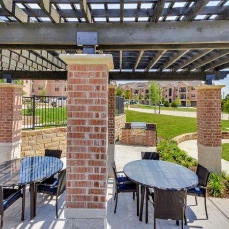 Beautiful view of our large outdoor courtyard. Two outdoor dinning tables with a set of four chairs each. One bbq grill.