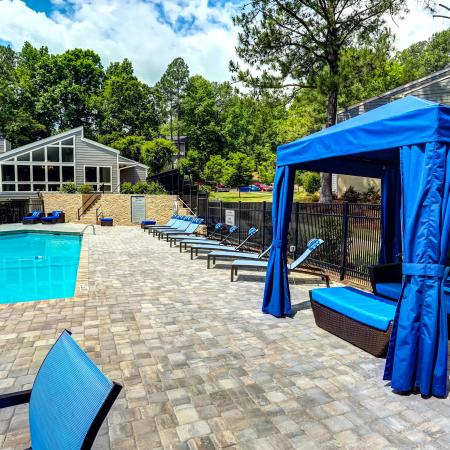 Pool surrounded by trees and sleek furniture and blue cabana