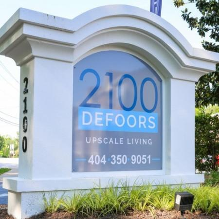 """Monument sign that says """"2100 Defoors Upscale Living"""""""