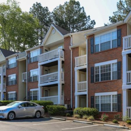 Exterior photo of 3 story apartment building, primarily made of brick with exterior balconies
