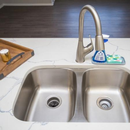 Beautiful stainless double kitchen sink with pull down stainless faucet and white marbled quartz countertops
