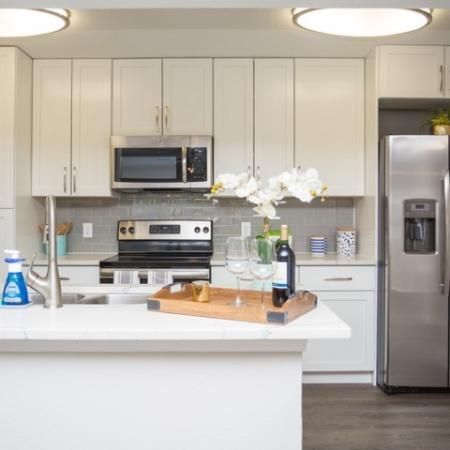 Modern Photo of Kitchen with white shaker cabinets with updated hardware package, modern lighting package, stainless steel appliances, quartz countertops, glass tile backsplash and wood plank inspired flooring