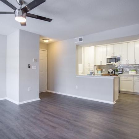 Beautiful renovated apartment interior with large open floorplan, 5 blade ceiling fan with light fixture, and view of renovated kitchen with stainless steel appliances and white shaker cabinets