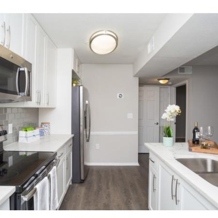 Modern Photo of Kitchen with white shaker cabinets with updated hardware package, modern lighting package, stainless steel appliances, quartz countertops, glass tile backsplash and plank inspired flooring