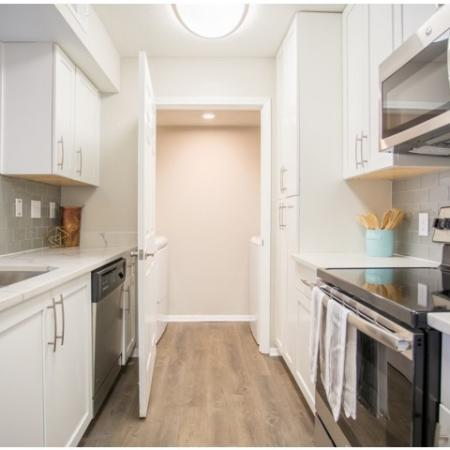 Modern Photo of Galley Kitchen with white shaker cabinets with updated hardware package, modern lighting package, stainless steel appliances, quartz countertops, glass tile backsplash and wood plank inspired flooring