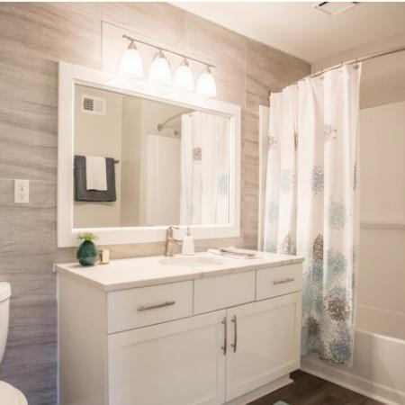 Renovated bathroom with ceramic tile walls, shaker style white cabinets with stainless pulls, designer lighting package and curved shower rod