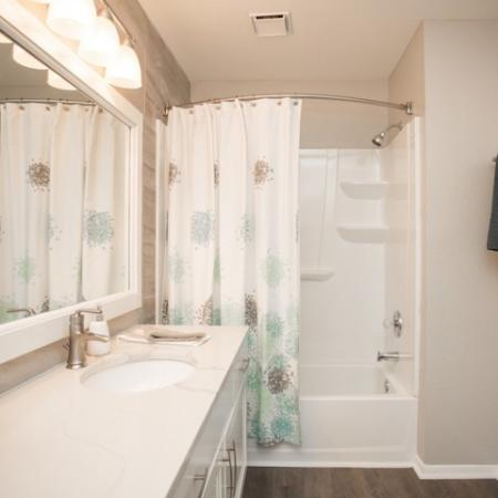 Renovated bathroom with shaker style white cabinets with stainless pulls, designer lighting package and curved shower rod