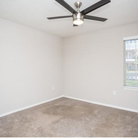 Corner photo of bedroom with plush neutral carpet, window and overhead 5 blade fan with light fixture
