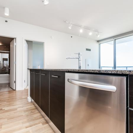 KItchen island with granite countertops, a stainless steel dishwasher and hardwood flooring