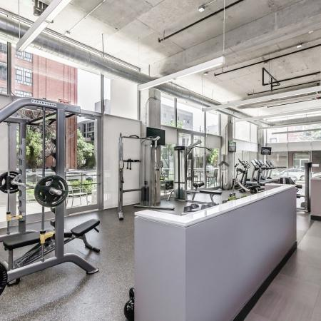Fitness center with exercise equipment, high ceilings, and floor-to-ceiling windows