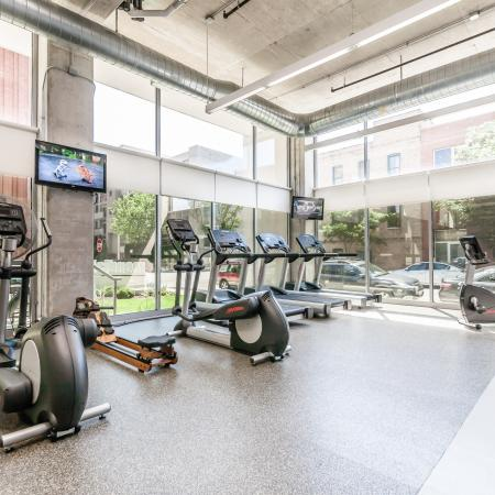 Fitness center with screen TVs, exercise equipment, high ceilings, and floor-to-ceiling windows with city views