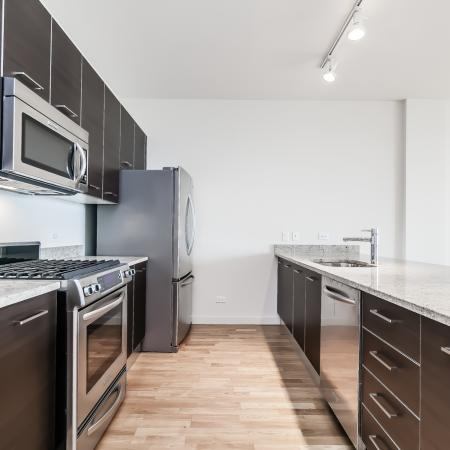 Furnished model kitchen with natural hardwood flooring, granite countertops, stainless steel appliances and the island