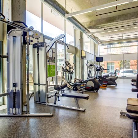 Fitness center with exercise equipment, high ceilings, and floor-to-ceiling windows with city views