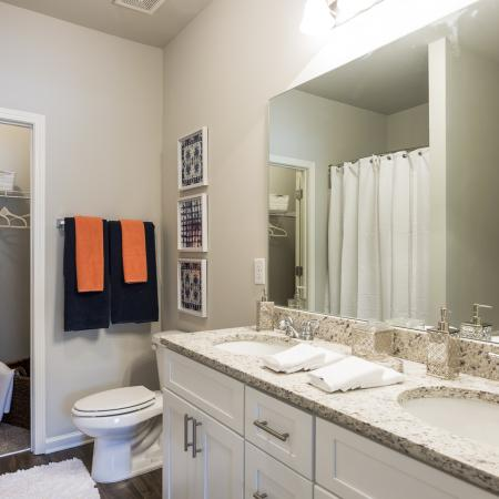 Bathroom with granite countertops and modern cabinetry