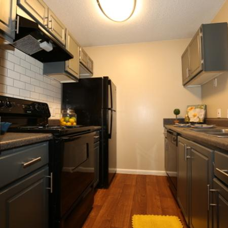 Recently renovated Kitchens with Black appliances, including White Tile back splash, Modern Light fixtures, Goose neck faucet & Brush nickel T-bar style pulls.