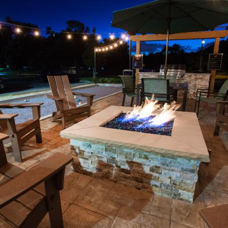 Fire pit at night with string lights above and wooden furniture