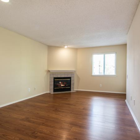 Large open living area with corner fireplace and wood flooring