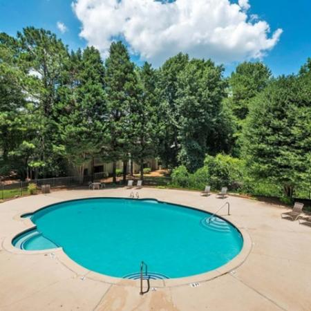 round swimming pool with large sundeck surrounded by trees