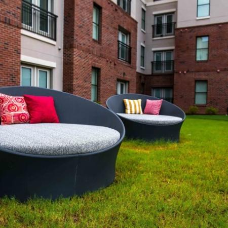 outdoor loungers with pillows on landscaping in courtyard