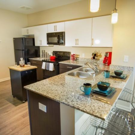 kitchen with pendant lighting, granite countertops, black appliances, roomy enough for a portable kitchen island