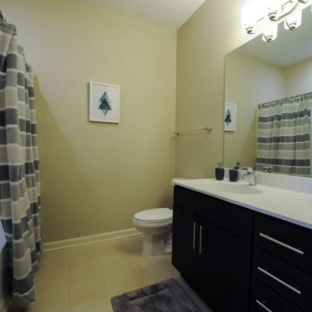 bathroom with white counters, showerbath combo and lots of drawer storage