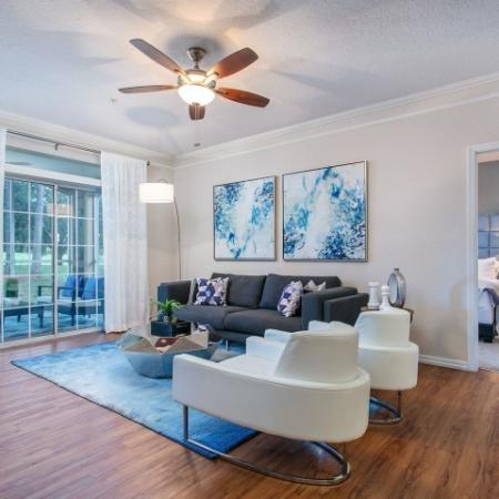 Alvista Metrowest Orlando Florida furnished model living room with vinyl plank flooring, ceiling fan with light, sliding patio door leading to screened in patio