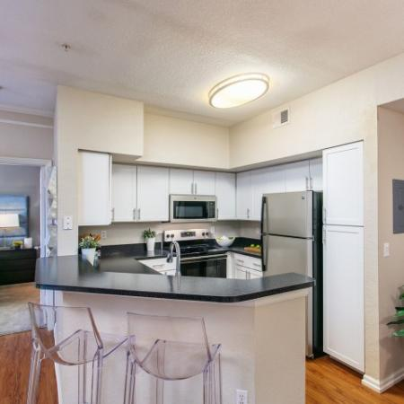 Alvista Metrowest Orlando Florida kitchen with stainless steel appliances, eat in kitchen bar with formica countertops, shaker style modern cabinets with handles and overhead light