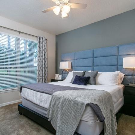 Alvista Metrowest Orlando Florida furnished model bedroom with carpeted floors, double window with blinds and ceiling fan with light