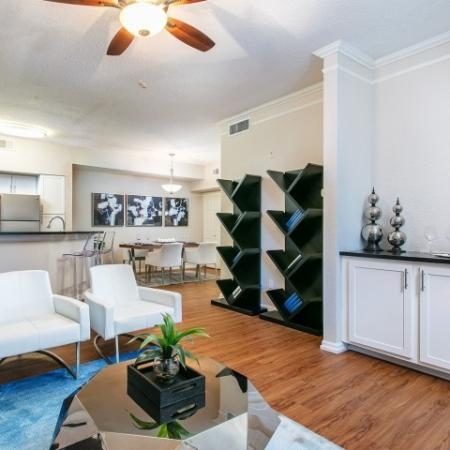 Alvista Metrowest Orlando Florida furnished model apartment with vinyl plank flooring, build in television stand and ceiling fan with light in living room, dining room and kitchen in background