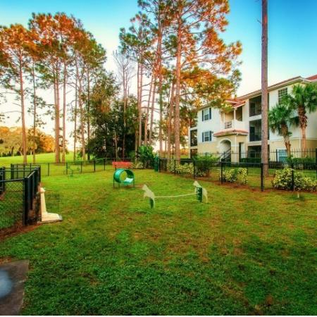 Alvista Metrowest Orlando Florida outdoor fenced bark park next to residential building with agility equipment.