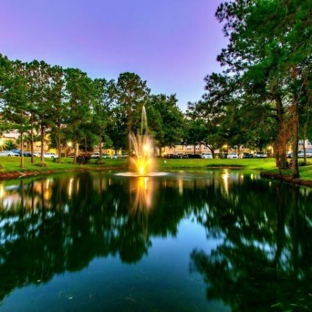Alvista Metrowest Orlando Florida community lake with mature landscaping at sunset with buildings in the background