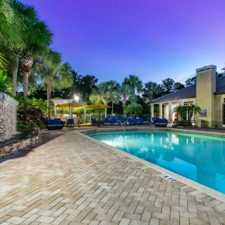 Alvista Metrowest Orlando Florida pool deck area with calm water, wall fountain, mature landscaping at sunset