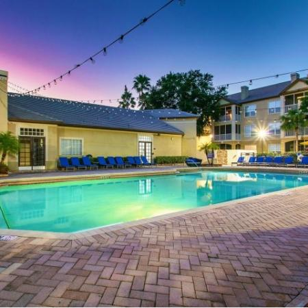 Alvista Metrowest Orlando Florida illuminated pool and clubhouse area at sunset with residential building int he background