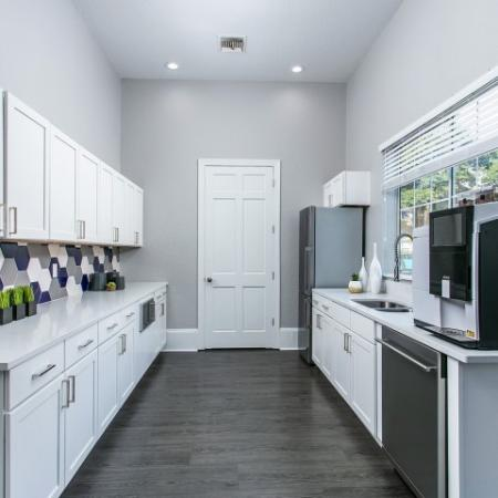 Alvista Metrowest Orlando Florida clubhouse commercial kitchen with stainless steel refrigerator and dishwasher, shaker style cabinets, coffee maker, double sink, double window with blinds, granite countertops and accent tile backsplash wit