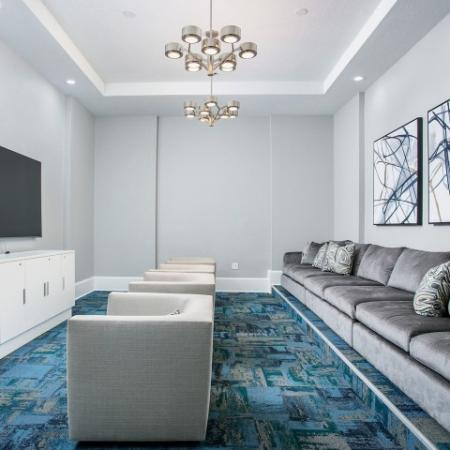 Alvista Metrowest Orlando Florida theater room with comfortable upholstered seating, wall mounted large flatscreen tv with cabinet underneath, overhead lighting and carpeted flooring