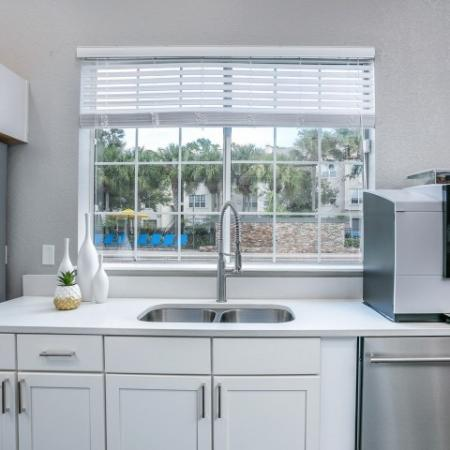 Alvista Metrowest Orlando Florida clubhouse  kitchen with double sink, gooseneck faucet, coffee maker, dishwasher, shaker cabinets, double window with blinds looking out to pool deck