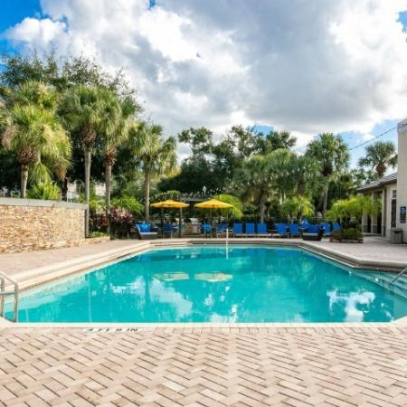 Alvista Metrowest Orlando Florida pool deck with pavers, sparkling pool, water fountain wall, poolside seating, hanging lights adjacent to clubhouse