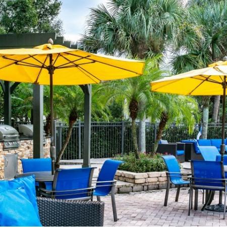 Alvista Metrowest Orlando Florida pool side table and chairs with umbrellas, built in grilling stations